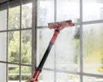woman cleaning window glass with steam in home