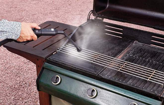 picture of a woman using a steam attachment to clean grease from a grill